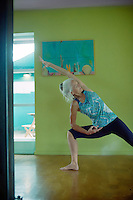 Mature woman practicing yoga inside.