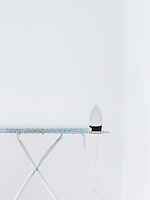 Iron on ironing board against white wall