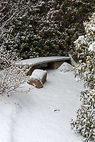 Snow covers a stone bench at the Asticou Azalea Garden, Northeast Harbor, Maine.
