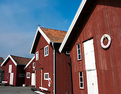 Traditional red wooden buildings beside harbour at Grundsund village on Swedens Bohuslan coast