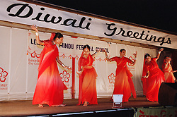 Women wearing traditional saris dancing together on stage to celebrate Diwali; festival of light,