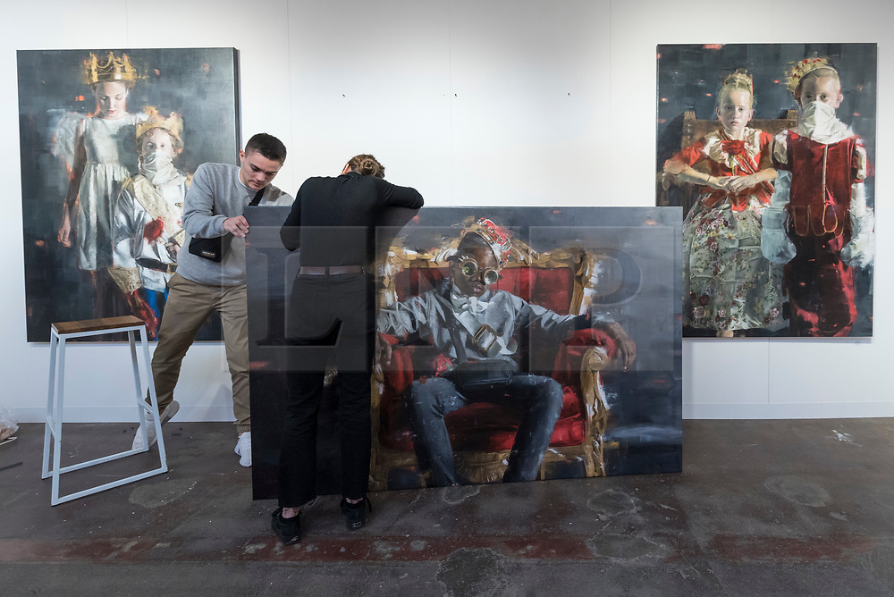 © Licensed to London News Pictures. 04/10/2018. LONDON, UK. Staff prepare to hang paintings by Kaili Smith. Preview of Moniker Art Fair, taking place during Frieze Week at the Old Truman Brewery, near Brick Lane.  Now in its tenth year, the fair embraces contemporary urban art from emerging and established artists  This year, the show's theme is 'Uncensored', shedding light on social, economic and ecological issues, and is open 4 to 7 October.  Photo credit: Stephen Chung/LNP