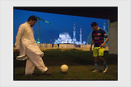 Immigrant workers' kickabout at dusk in the middle of a highway intersection near the largest mosque of the United Arab Emirates. Abu Dhabi, January 13, 2017.