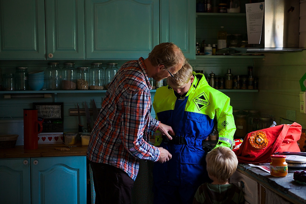 Bjornar Hogset helps his son-in-law Oystein put on his first fisherman survival suit in the kitchen of their home in Sorland, Vaeroy Island, Lofoten Islands, Norway.