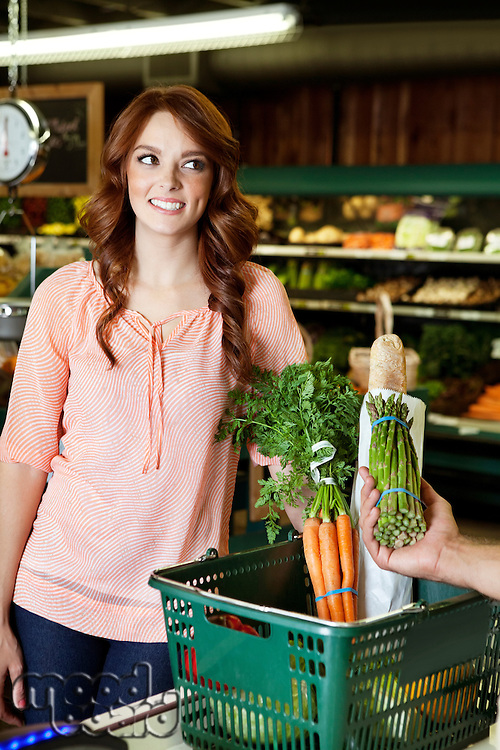 Happy young woman looking away while hand holding vegetable in supermarket