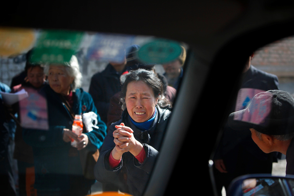A Chinese Petitioners approach a car, blocking the vehicle's way, as they plead to show their grievances, near a local government office supposed to receive petitions in  Beijing, China, Friday, Feb.27, 2009. Police have taken away more than 1,000 petitioners looking to air their grievances ahead of the annual meeting of China's legislature, supporter of the petitioners said. Widespread frustration with the petition system is simmering and in several recent cases has boiled over, with a handful of people making desperate bids for attention. The peak season for the pilgrimages is the beginning of March, when China's lawmakers gather in the capital for their once-a-year legislative session. In an acknowledgement that the petition system is in crisis, China's Premier Wen Jiabao vowed to improve legal channels for grievances.