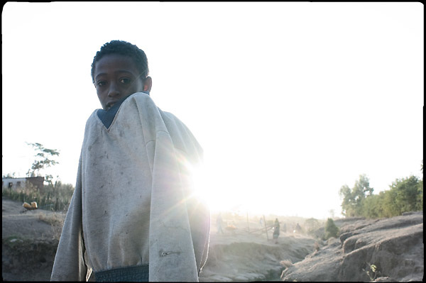 """A young boy gets hot under the first rays of morning sun, in Shashemene, South Ethiopia, on wednesday, March 19 2008.....""""Shashamene or Shashemene (ethiopian name), located in the Oromia Region of Ethiopia, is """"the place"""", the ancestral homeland. For the whole Rastafarians repatriation to Africa or to Zion or to the Promise Land is the first goal. Rastas assert that """"Mount Zion"""" is a place promised by Jah and they  claim themselves to represent the real Children of Israel in modern times. During the last years of the 40's, Emperor Haile Selassie I, considerated from that movement incarnation of God, donated 500 acres of his private land to members and other settlers from Jamaica including other parts of the Caribbean..The Rastafarian settlement in Shashamane was recently reported to exceed two hundred families. In January 2007 it organized an exhibition and a bazaar in the city. It was also reported recently prior to the Ethiopian Millennium that various pro-Ethiopian World Federation groups, consisting of indigenious Ethiopians and Rastafarians, have given support to one of many five year plans proposed for sustainable development of Shashamene, Ethiopia."""""""