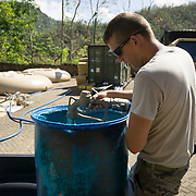 OCTOBER 25 - UTUADO, PUERTO RICO - <br /> Spc Wade Scamehorn helps residents fill containers with potable water at a station next to the Lago Dos Bocas in Utuado. Troops from Fort Bragg, NC, are using a water filtration system to purify the liquid.<br /> (Photo by Angel Valentin/Freelance)