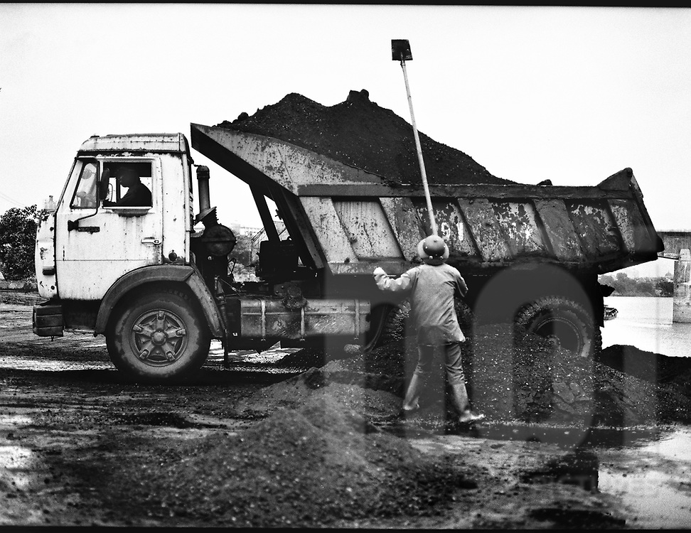 A vietnamese worker loads archoal on a truck with a shovel. Harbour along the red river in Hanoi, Vietnam, Asia