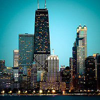 Photo of Chicago downtown at night. Includes the John Hancock Center building which is one of the world's tallest skyscrapers and is a famous fixture in the Chicago skyline. Image is high resolution and toned green.