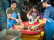 14 AUGUST 2015 - BANGKOK, THAILAND:   Workers cut up fresh fish in an alley next to Saphan Pla fish market in Bangkok. Saphan Pla fish market is the wholesale fish market that serves Bangkok. Most of the fish sold in Saphan Pla is farmed raised fresh water fish. The market is open 24 hours but it's busiest in the middle of the night and then again from about 7.30 until 11 in the morning.      PHOTO BY JACK KURTZ