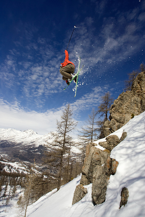 Skier jumping off rock