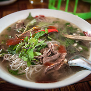 A fresh bowl of beef noodle soup, a staple of Lao cuisine, in a morning market in northern Laos.