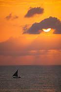 A silhouetted, traditional dhow boat sails on the Indian Ocean off Stone Town on the coast of Zanzibar. Tanzania is in East Africa. http://www.gettyimages.com/detail/photo/dhow-and-sunset-off-zanzibar-tanzania-royalty-free-image/92063749
