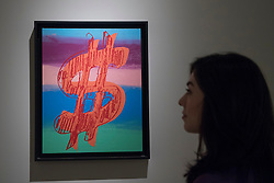 "© Licensed to London News Pictures. 29/06/2017. London, UK.  A woman views ""Dollar Sign"", 1981, by Andy Warhol.  Members of the public visit Masterpiece London, a leading art fair held in the grounds of the Royal Hospital Chelsea.  The fair brings together 150 international exhibitors presenting works from antiquity to the present day and runs 29 June to 5 July 2017.  Photo credit : Stephen Chung/LNP"