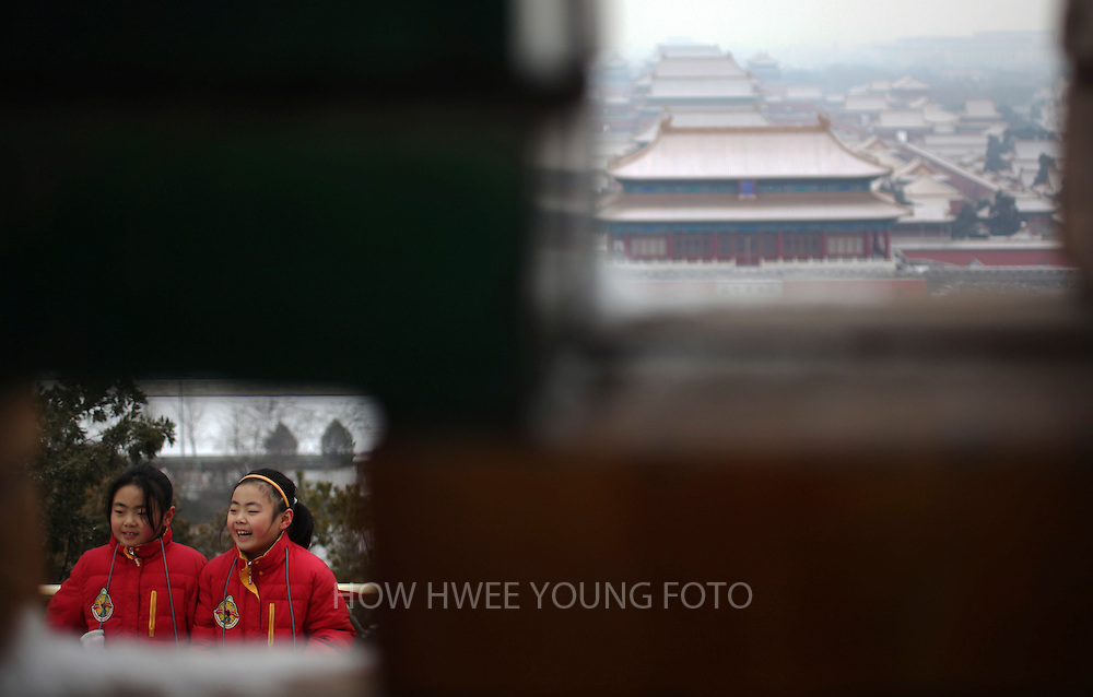 epa03051787 Chinese girls and a view of the forbidden city is seen through little windows in the walls of the Jingshan park in Beijing, China, 07 January 2012. China announce 06 January it will publish more detailed air quality data on Beijing later this month based on an international standard known as PM 2.5, which measures tiny particles that are 2.5 microns or less in diameter. This announcement follows protestations from the public over official readings that understate the severity of air pollution in the city.  EPA/HOW HWEE YOUNG