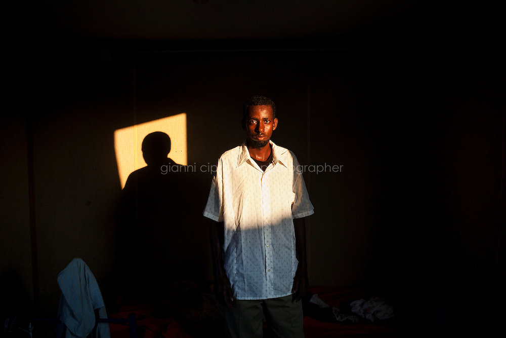 Hal Far, Malta - 20 August, 2012:  Somali migrant Daher Abdi Ali, 28, stands in fron of his bed in the container he lives in and that he shares with other 9 migrants in the Hal Far Hangar Site in Hal Far, Malta, on 20 August, 2012.<br /> <br /> The Hangar Open Center is a field with an ex-aircraft hangar which, until 2011, included Swiss Red Cross tents in a dark, non lit space in very poor conditions and with inflamable oil on the floor. Today, the hangar is closed and the migrants live in 34 external containers with no water. <br /> <br /> The Open Centres in Malta serve as a temporary accomodation facility, but they ended becoming permanent accomodation centres, except for those immigrants who receive subsidiary protection or refugee status and that are sent to countries such as the United States, Germany, Poland, and others. All immigrants who enter in Malta illegally are detained. Upon arrival to Malta, irregular migrants and asylum seekers are sent to one of three dedicated immigration detention facilities. Once apprehended by the authorities, immigrants remain in detention even after they apply for refugee status. detention lasts as long as it takes for asylum claims to be determined. This usually takes months; asylum seekers often wait five to 10 months for their first interview with the Refugee Commissioner. Asylum seekers may be detained for up to 12 months: at this point, if their claim is still pending, they are released and transferred to an Open Center.<br /> <br /> Gianni Cipriano for The New York Times