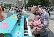 Seth Johnson and his daughter Phoebe, enjoy Father's Day by playing one of the 88 Sing for Hope Pianos, supported by Chobani, Inc., at the Josie Robertson Plaza at Lincoln Center, Sunday, June 16, 2013. The event celebrates the conclusion of the Sing for Hope Pianos project, a two-week public art installation around the five boroughs of New York.  (Photo by Diane Bondareff/Invision for Sing for Hope)