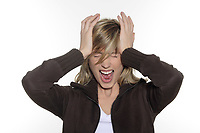 portrait in studio on a white background of a young blond caucasian expressive woman screaming having a headache and holding her head