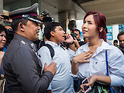 22 MAY 2015 - BANGKOK, THAILAND:  Anti-coup activists SIRIWAT SERITHIWAT (center on phone) and NATCHACAH KONG-UDOM (right) talk to a Thai police officer at Lat Phrao subway at the start an anti-coup protest.  The Thai military seized power in a coup on May 22, 2014. There were small protests throughout Bangkok Friday to mark the first anniversary of the coup. Police arrested protestors at several locations. The most serious protest was at Bangkok Art and Culture Centre (BACC) where about 100 protestors, mostly students, faced off against police for several hours. Police made numerous arrests at the BACC protest.    PHOTO BY JACK KURTZ