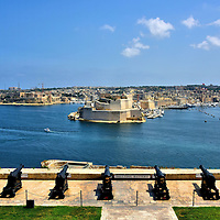 Saluting Battery in Valletta, Malta<br /> This Saluting Battery points towards the Grand Harbour.  It was called the Porto delle Galere when the Knights Hospitaller ruled Malta starting in 1565. The year before the Ottomans located cannons here so they could bombard Fort St. Angelo in the center. That fortress was a castle called Castrum Maris during medieval times. When the Turks were defeated in 1566, the Saints Peter and Paul&rsquo;s Bastion was built.  This vantage point from the Upper Barrakka Gardens gives you the best view of the guns when they are fired at noon and 4:00 every day. From here you can also see Fort Ricasoli on the distant left.