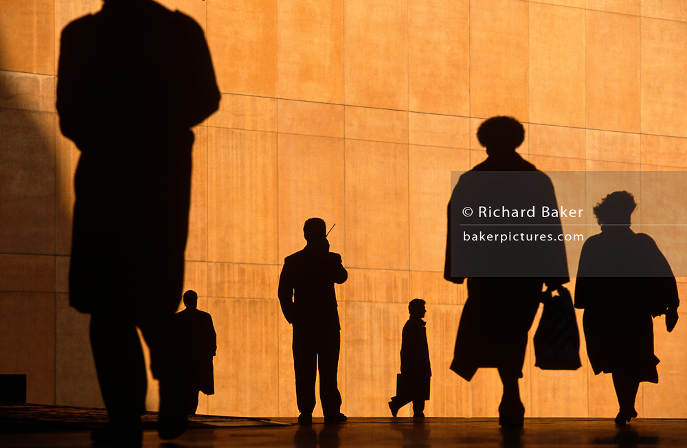 Six office workers silhouetted against the large orange wall of the Credit Lyonnais Bank. They rush to work while one figure stands and talks into his mobile phone, at Broadgate in the City of London, UK. Broadgate Estate is a large, 32 acre (129,000 m²) office and retail estate in the City of London, owned by British Land and managed by Broadgate Estates. It was originally built by Rosehaugh and was the largest office development in London until the arrival of Canary Wharf in the early 1990s.