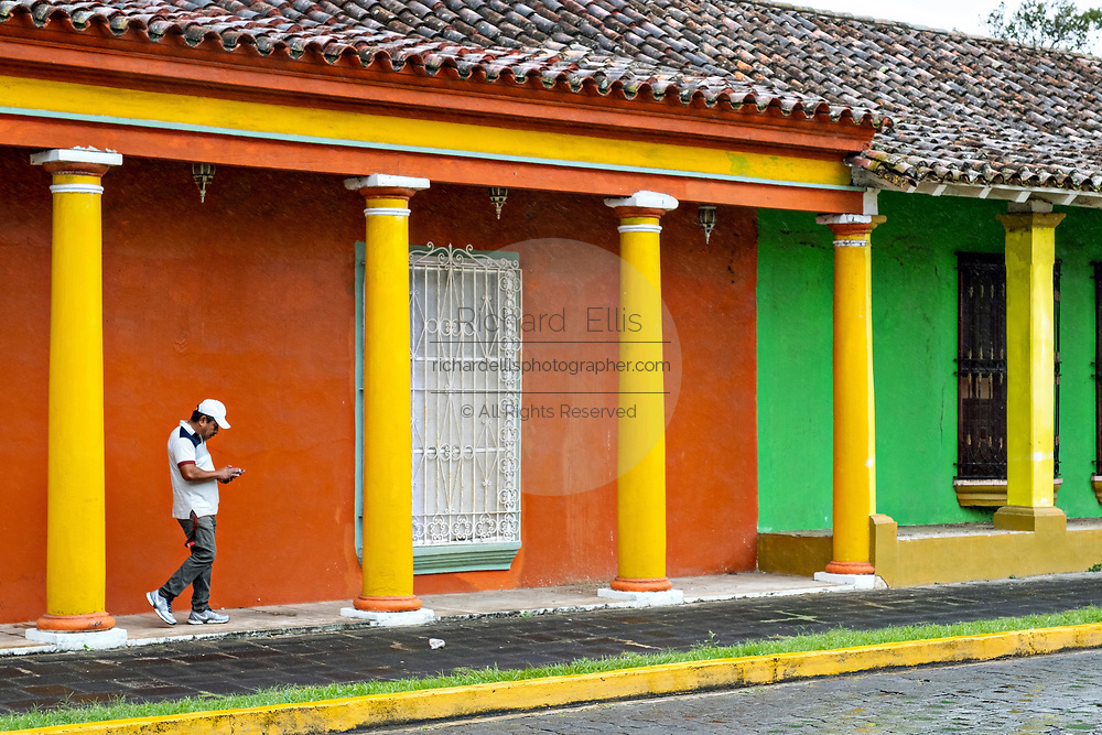 A man walks past brightly painted colonnaded style homes in Tlacotalpan, Veracruz, Mexico. The tiny town is painted a riot of colors and features well preserved colonial Caribbean architectural style dating from the mid-16th-century.
