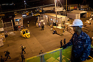 A navy sailor watches as relief supplies are loaded on board the USNS Comfort, a naval hospital ship,  before its mission to help survivors of the earthquake in Haiti on Friday, January 15, 2010 in Baltimore, MD.