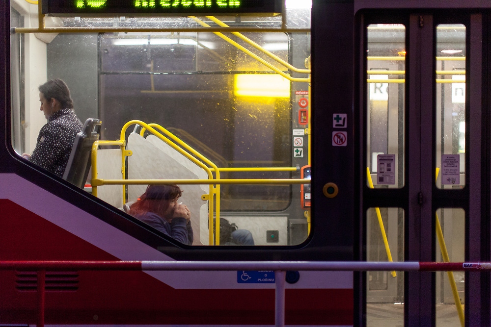 """A woman cleaning her nose with a tissue at the tram stop """"Biskupcova"""" street in Prague Zizkov during an early morning and after the Coronavirus pandemic (COVID-19) outbreak - pictured on the 11th of March 2020."""