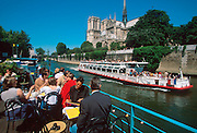 FRANCE, PARIS, LATIN QUARTER traditional river barges now cafes moored along the Quai de Montebello with Notre Dame Cathedral beyond
