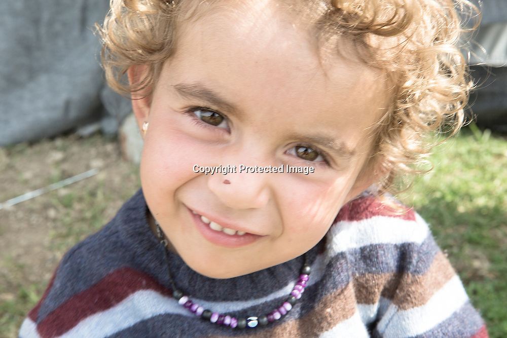 Young Syrian refugee poses for a picture in Eko station a makeshift camp located near by Polykastro, Greece where she is being living for last few months since Macedonia closed the border with Greece.