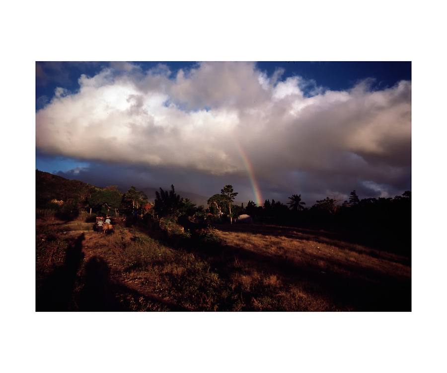 A rainbow appears on a distant horizon as villagers make their way home in rural Haiti. ©Ed Hille