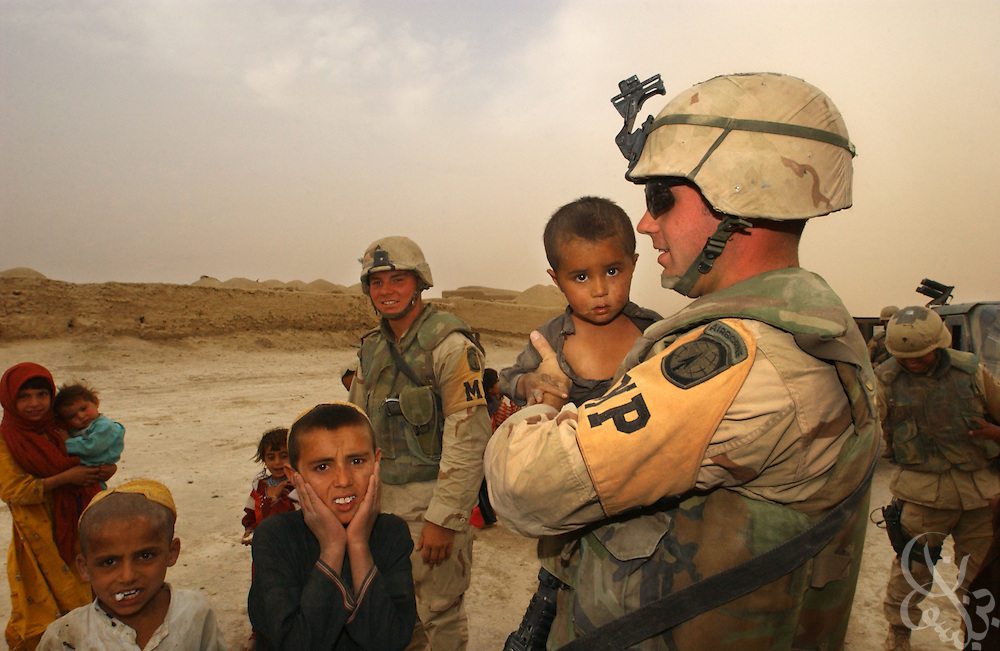 Members of the U.S. Army  3rd Platoon 108 MP company play with local Afghan children as they patrol May 12, 2002 near the Kandahar airfield in southern Afghanistan. U.S. soldiers routinely patrol the area as part of the ongoing coalition Operation Enduring Freedom.