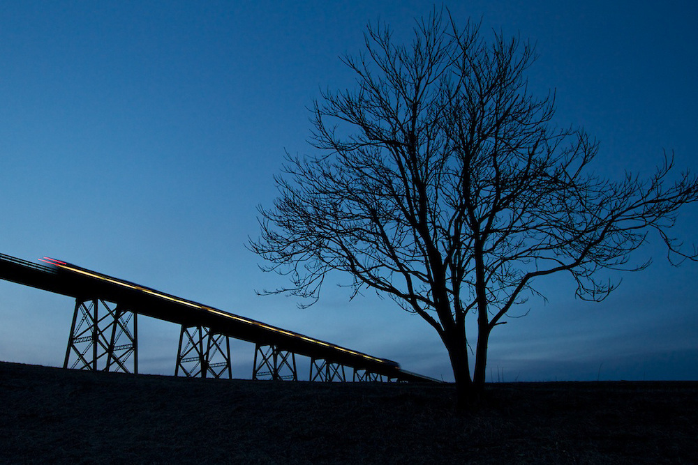 The sun has gone down, stars are just starting to appear overhead, and commuters are still making their way home from Hoboken to close a long day. Metro North train #57 crosses Moodna Viaduct in Salisbury Mills, NY on its journey to Port Jervis.