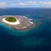 Aerial panorama of Lua Ui Island in the Vava'u island group of the Kingdom of Tonga., with a boat in frame for scale. From this vantage point it is clear that the visible portion of the island structure is surrounded by extensive reef structure.