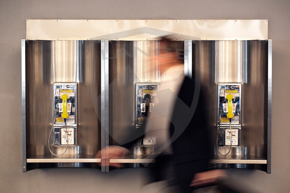 man passing pay telephones.