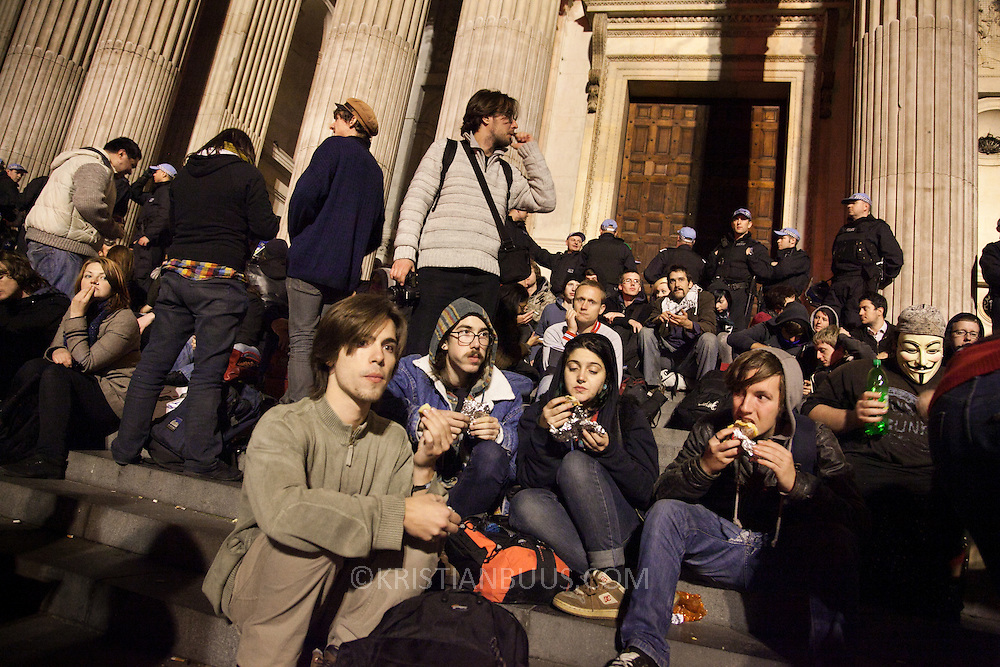 Baked potatoes and cheese has been delivered and handed out by volunteers to feed the protestors stuck inside the police cordon. The London Stock Exchange was attempted occypied in solidarity with Occupy Wall in Street in New York and in protest againts the economic climate, blamed by many on the banks. Police managed to keep people away fro the Patornoster Sqaure and the Stcok Exchange and thousands of protestors stayid in St. Paul's Square, outside St Paul's Cathedral. Many camped getting ready to spend the night in the square.
