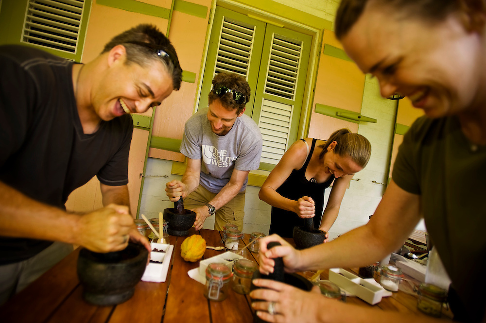 "Tourists grind cocoa beans with a mortar-and-pestal while learning to make chocolate during a ""Bean to Bar"" class at Hotel Chocolat on the Rabot Estate in St. Lucia, taught by Chef Ron Lafeuille, who might as well have Ph.D. in cocoa and can thus drop every name in the storied history of the fruit, from colonizers to Cadbury."