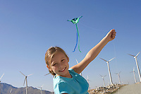 Girl (7-9) with kite on wind farm portrait