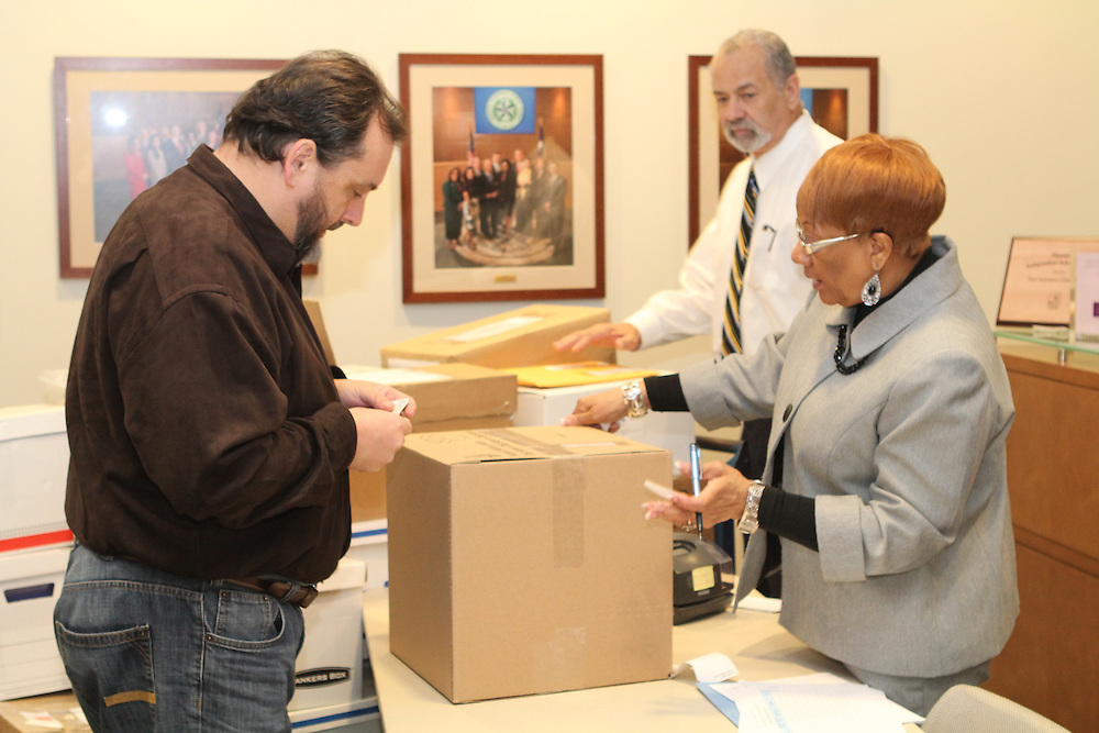 Brenda Adams, budgeting accounting clerk in Procurement, accepts an RFQ from Edward Strauss (left) of Architect Strauss in Cypress. Elvis Eaglin, senior manager in Procurement(center), was on hand to supervise the submissions.