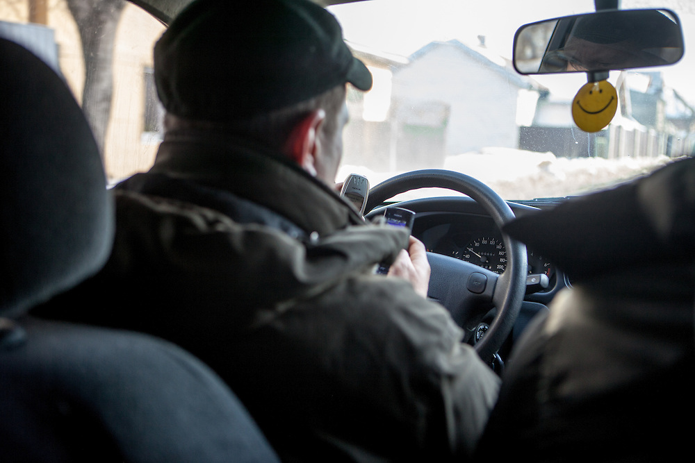 Activist Oleg driving a car and handling two mobile phones at the same time during a car ride to the citycenter of Lviv, Ukraine.