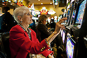 Senior woman playing a slot machines, Atlantic City, NJ, New Jersey, USA