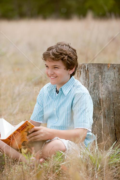 Boy reading a book outdoors