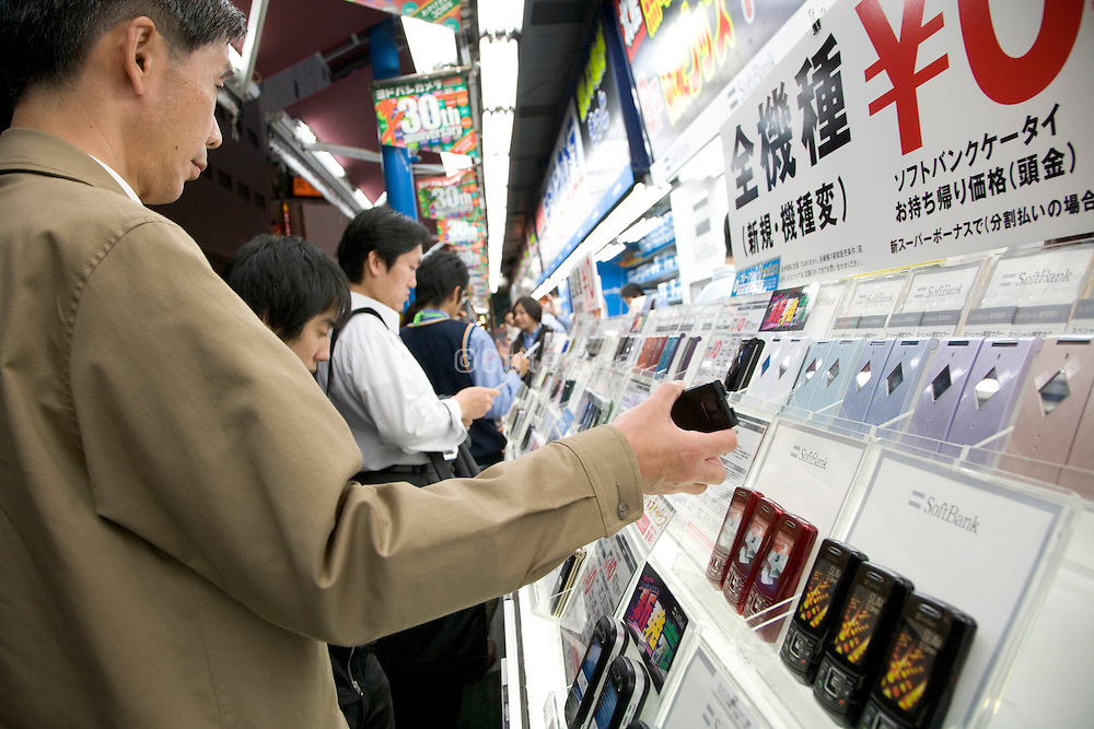 Japanese businessmen looking for the latest mobile phone