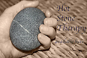 "Hand holding massage hot stone with wicker background. Copy reads ""Hot Stone Therapy available here"""