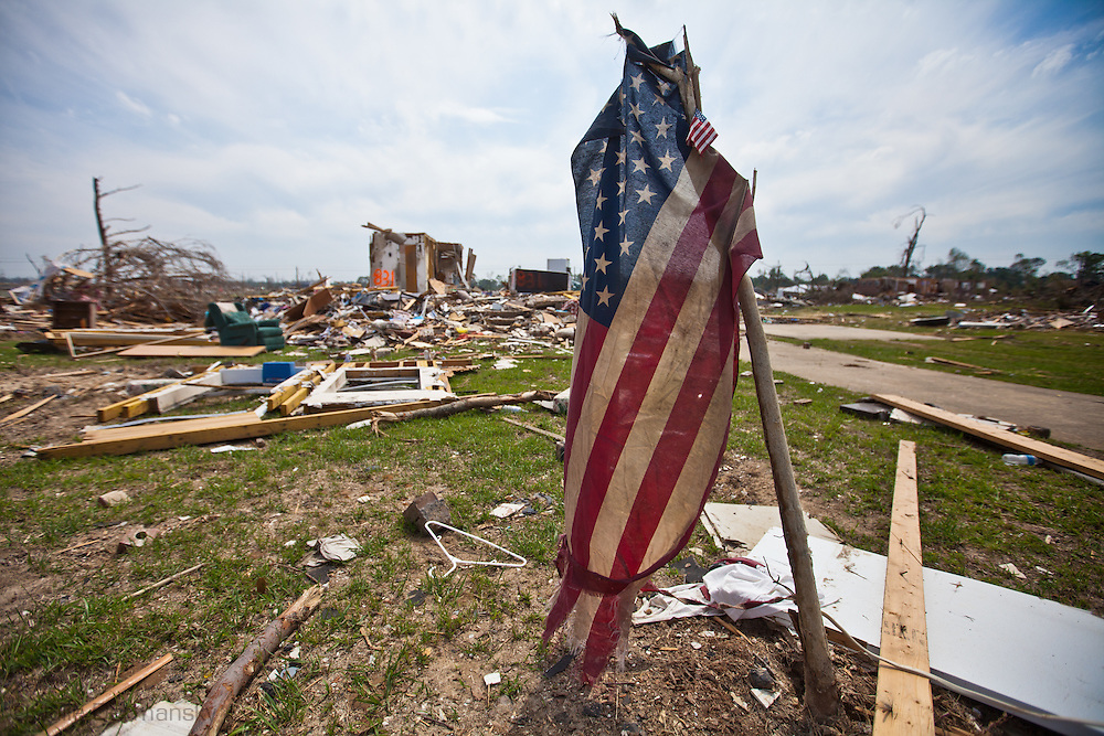 an American flag in front of a home totaled by a tornado in Pleasant Grove, a suburb of Birmingham Alabama. Pleasant Grove remains in a state of ruin over two weeks after it was hit by an F-4 ( possibly an F-5) tornado, one of an estimated 300 that struck Alabama and the neighboring states on April 27th .