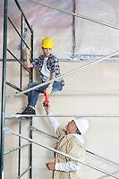 Male worker giving drill to woman on scaffold at construction site