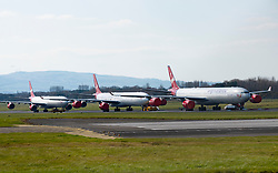 Prestwick, Scotland, UK. 22 March, 2020. Three Airbus A340 aircraft owned by Virgin Atlantic parked and in storage at Glasgow Prestwick airport. Many airlines have parked surplus aircraft at the airport and at others across the UK because passenger numbers and flights have plummeted during the Coronavirus pandemic. Iain Masterton/Alamy Live News.