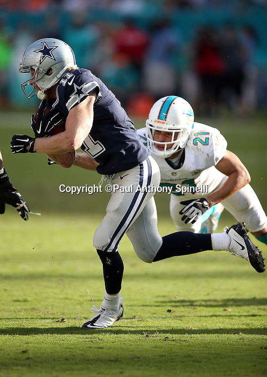 Dallas Cowboys wide receiver Cole Beasley (11) tries to elude a diving tackle by Miami Dolphins cornerback Brent Grimes (21) as he catches a pass and runs for a key late fourth quarter first down that eats the clock during the 2015 week 11 regular season NFL football game against the Miami Dolphins on Sunday, Nov. 22, 2015 in Miami. The Cowboys won the game 24-14. (©Paul Anthony Spinelli)
