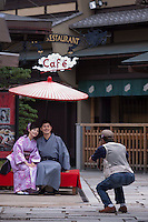 A couple on holiday have their photograph taken in traditional Japanese dress on the streets of Kyoto near Kiyomizudera Temple, Japan.
